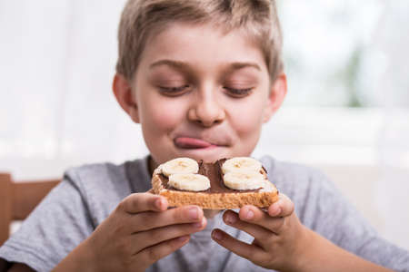 tastes: Happy boy eating delicious sandwich with banana and chocolate cream