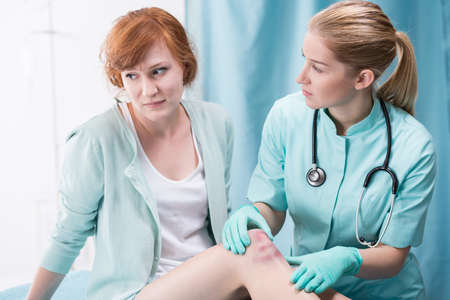 diagnosing: Image of doctor diagnosing female patient with leg wound