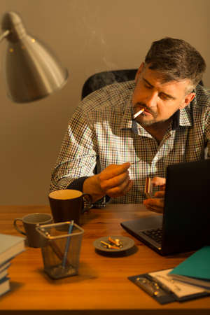 untidy: Picture of smoking bearded man at untidy desk Stock Photo