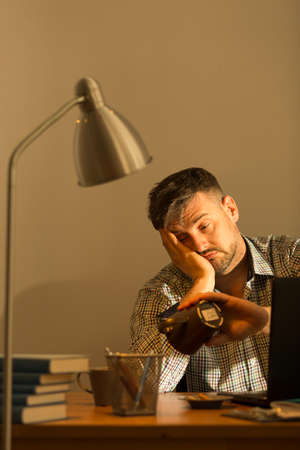 isolation: Photo of exhausted handsome man sitting at desk Stock Photo
