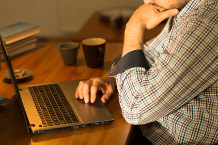 isolation: Close up of focused man using laptop sitting at desk