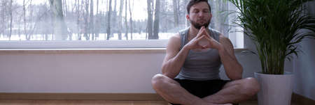 restfulness: Panoramic view of cross-legged meditating young man