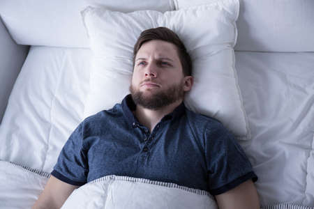 day bed: Depressed man suffering from insomnia lying in bed Stock Photo