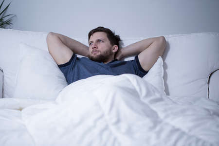 sleeplessness: Young handsome man lying in bed fully awake