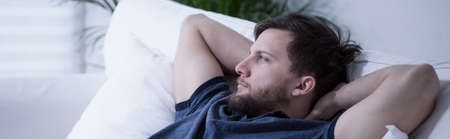 alone sad: Panoramic view of thoughtful man lying on bed