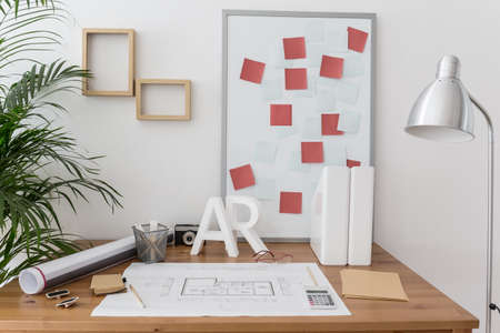 messy house: Office of professional home designer with plans and sketches Stock Photo
