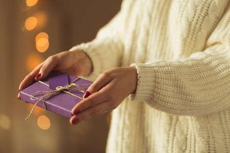 dar un regalo: Woman giving xmas present wrapped in violet paper Foto de archivo