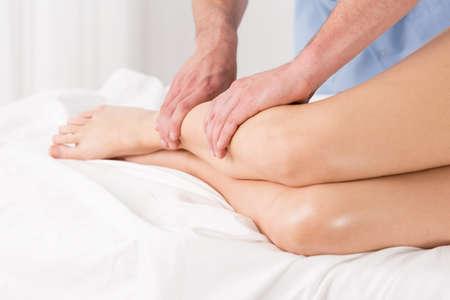 massaggio: Fisioterapista facendo linfodrenaggio per le gambe Archivio Fotografico
