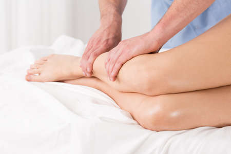 lymphatic: Physical therapist doing lymphatic drainage for the legs Stock Photo