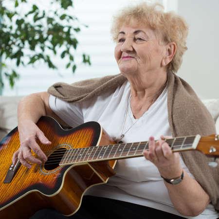 señora mayor: Mujer feliz edad tocando la guitarra en su habitación Foto de archivo
