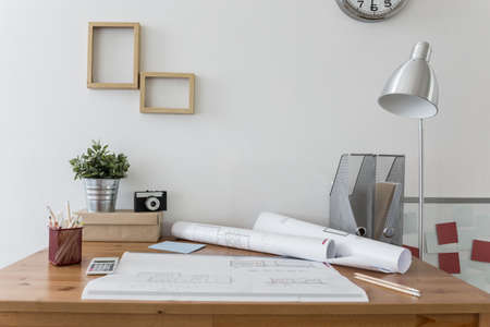 architect office: Messy desk with architects plans on it Stock Photo