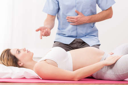 breathing exercise: Pregnant woman lying and doing breathing exercise
