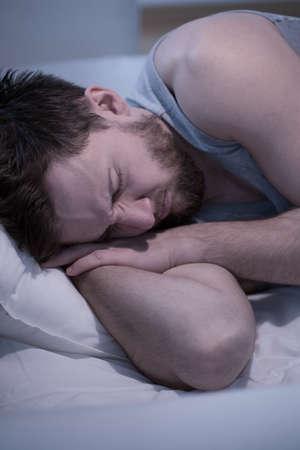 cansancio: Hombre joven que duerme tener una mala pesadilla