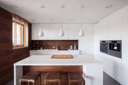 kitchen cabinet: White kitchen island in modern and wooden kitchen