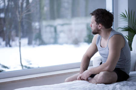 tiresome: Sad man looking through the window in his bedroom Stock Photo