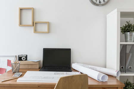 work from home: Desk in the creative office with laptop and architects plan Stock Photo