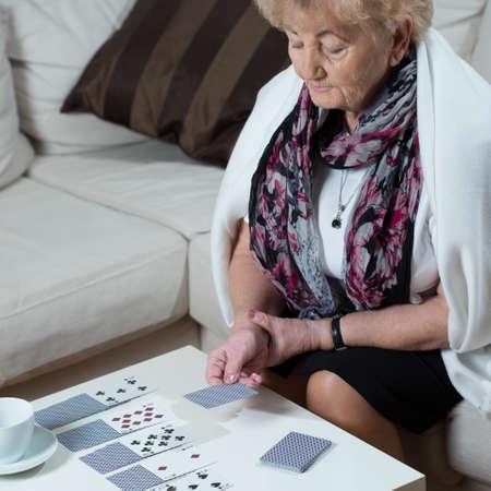 bonne aventure: Senior femme assise sur le canapé et jouer aux cartes seuls Banque d'images