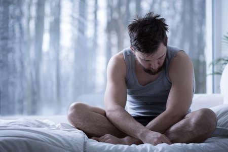 insomniac: Depressed insomniac man sitting on bed in daylight Stock Photo