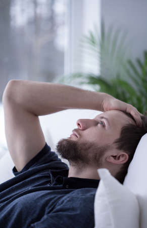 insomniac: Worried frustrated young man cannot go to sleep
