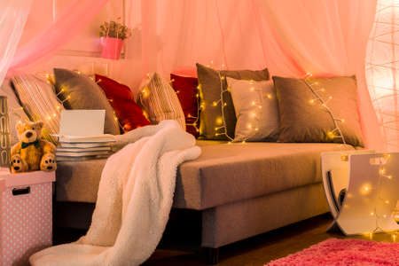 cosy: Picture of stylish cosy bed with decorative lighting Stock Photo