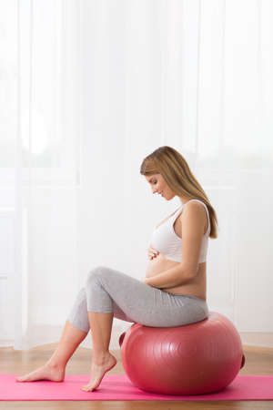 pregnant exercise: Photo of healthy pregnant lady exercising with ball