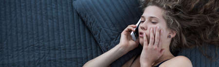 woman laying: Woman is talking on phone in bed