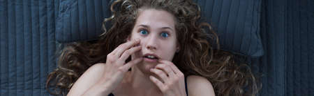 panorama: Young beautiful woman is scared after nightmare