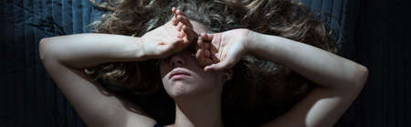 psychical: Woman in bed has headache because of insomnia