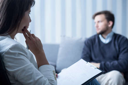 Young female psychiatrist talking with despair patient Stockfoto