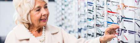 expositor: Mujer mayor sonriente en la tienda de moda óptica