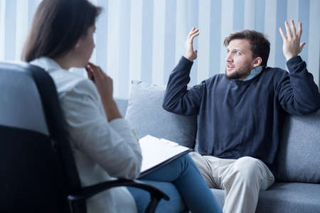 esquizofrenia: Hombre con esquizofrenia durante la psicoterapia en el consultorio del psiquiatra