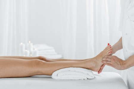 Masseur massaging female foot in wellness center
