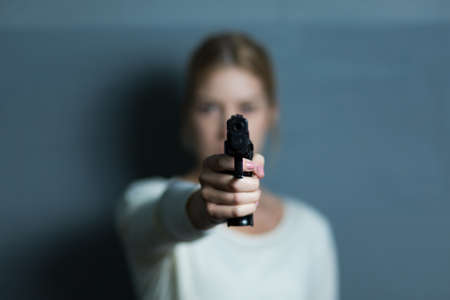 murdering: Mad woman pointing a gun at someone Stock Photo