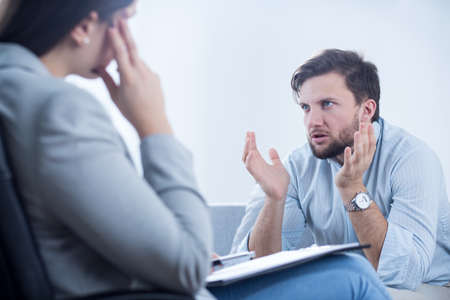 Angry man talking with psychiatrist or psychologist