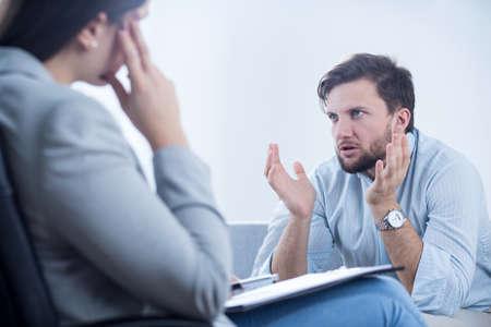 enfado: El hombre enojado hablando con psiquiatra o psicólogo