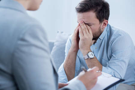 homme triste: Homme avec la dépression à pleurer lors de la séance de psychothérapie Banque d'images