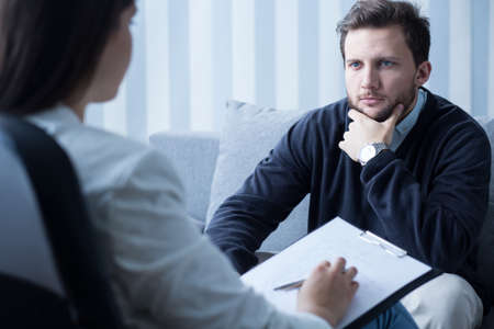 Young man during therapy at psychologist's office Stock Photo