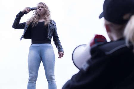 mujer policia: Mujer policía con megáfono hablando con la muchacha de suicidio
