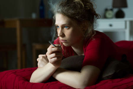 blond girl: Pensive young woman smoking cigarette in room