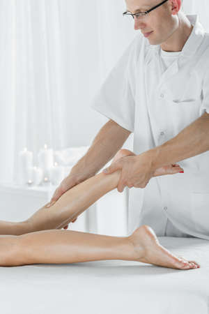 women legs: Image of physiotherapist doing massage of calf Stock Photo
