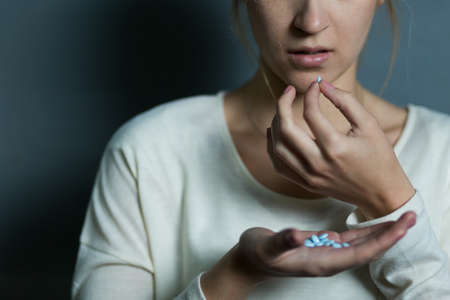 drug overdose: Depressed girl taking a lot of drugs