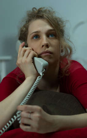 miserable: Young miserable woman talking on the phone