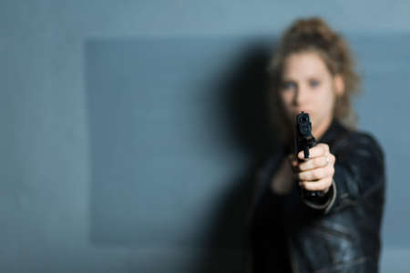 mental disorder: Female murderer with gun aiming at someone