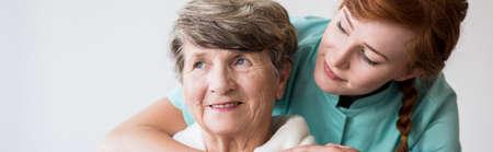 Zieke oudere glimlachende vrouw en haar jonge verzorger