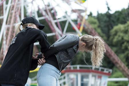 Polizia che arresta criminale femminile nel parco di divertimenti Archivio Fotografico - 47867429