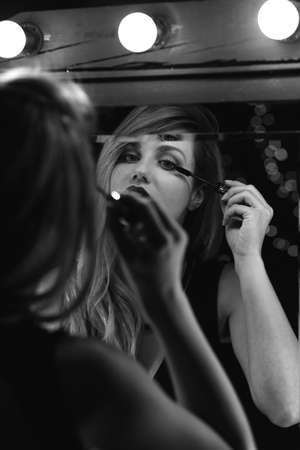 get dressed: Vertical view of attractive female doing her make-up for date Stock Photo