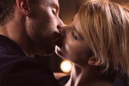 Horizontale weergave van een knappe paar French kiss 's nachts Stockfoto