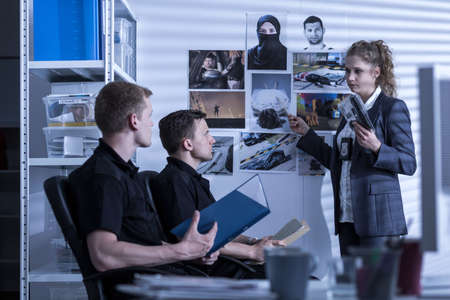 Detective della polizia e gli ufficiali stanno guardando le foto Archivio Fotografico - 48079262