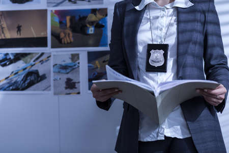station: Police woman is reviewing files and documents Stock Photo
