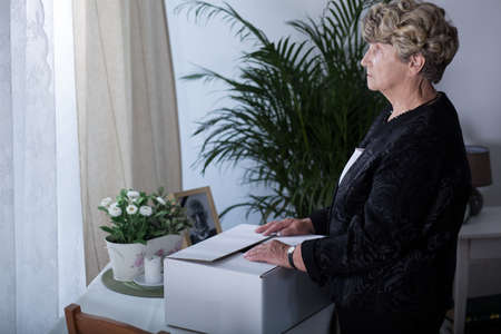 widow: Sad widow holding box of memories at home